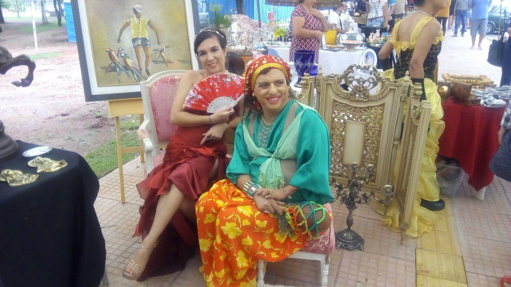 Valquíria Vital e Condessa Valéria Vaz, na Feira de Antiguidades da Praça Tamandaré. As duas estão sentadas juntas, com roupas e maquiagem relacionadas ao evento de época.