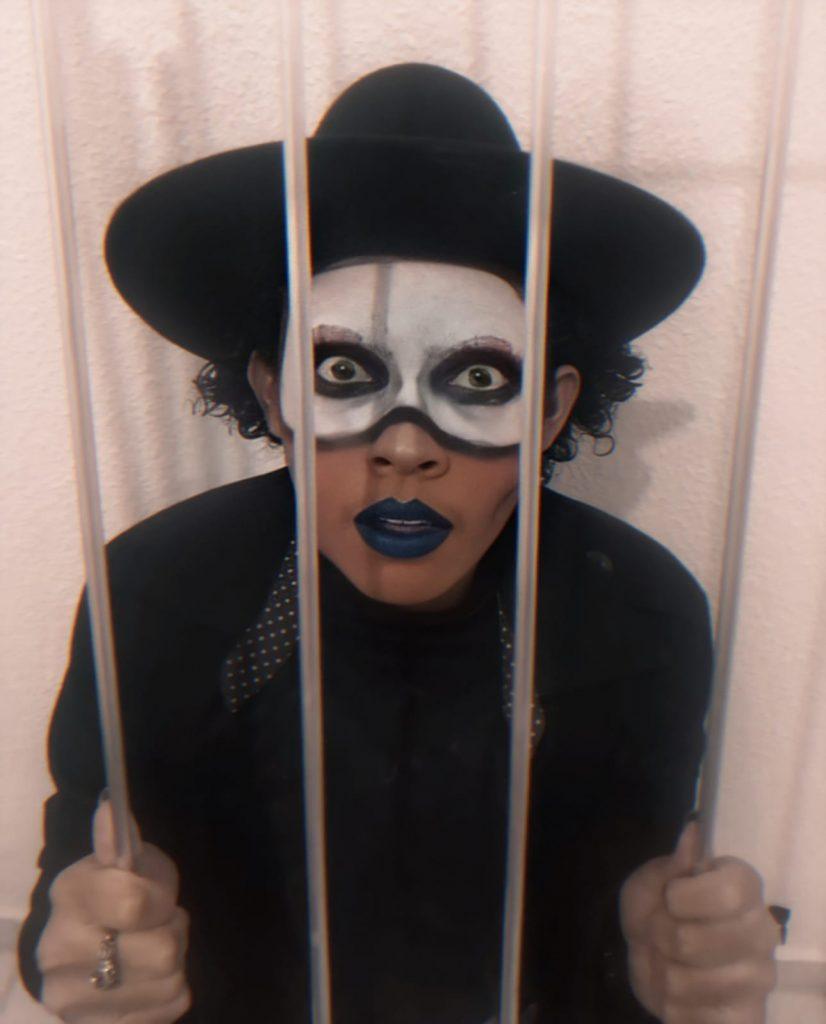 Uma fotografia do escritor David Gomes, montado com o figurino Drag Queer. Seu personagem é Dite Bowery, e possui um visual mais gótico, com uma roupa e chapéu preto e uma maquiagem mais dark.