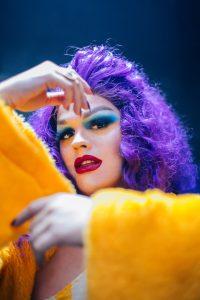 A drag queen Guilhotina Guinle, em uma pose que mostra todo seu figurino: unhas feitas, cabelo, maquiagem e roupa.