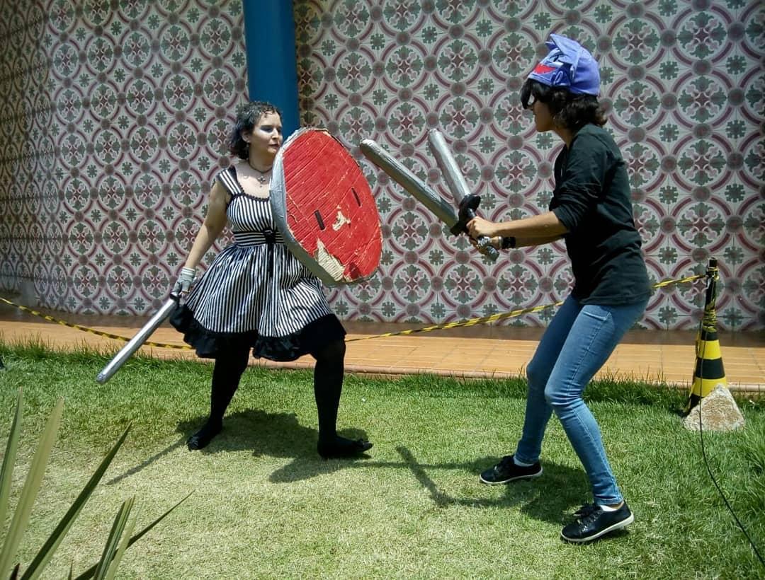 Na fotografia, uma luta de batalha medieval em um dos eventos do SESC Geek. À esquerda, Caroline Pinheiro segurando espada e escudo. À direita, Kássia Nunes com duas adagas.
