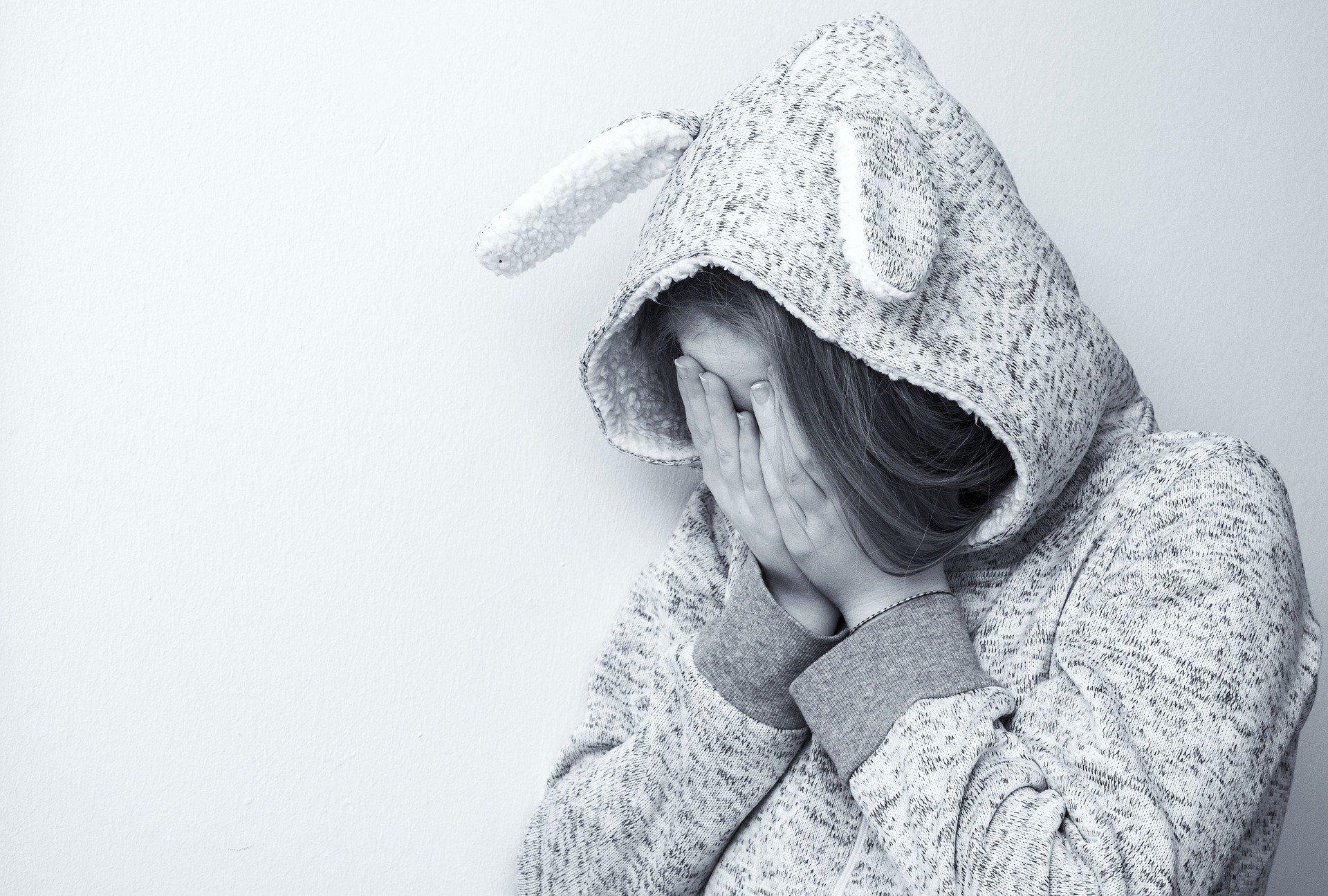 """Na imagem, uma pessoa com as mãos tampando o rosto, mostrando tristeza profunda. A pessoa usa uma roupa de pelúcia, com touca de orelhas compridas. Imagem de <a href=""""https://pixabay.com/pt/users/anemone123-2637160/?utm_source=link-attribution&utm_medium=referral&utm_campaign=image&utm_content=2048905"""">Anemone123</a> por <a href=""""https://pixabay.com/pt/?utm_source=link-attribution&utm_medium=referral&utm_campaign=image&utm_content=2048905"""">Pixabay</a>"""