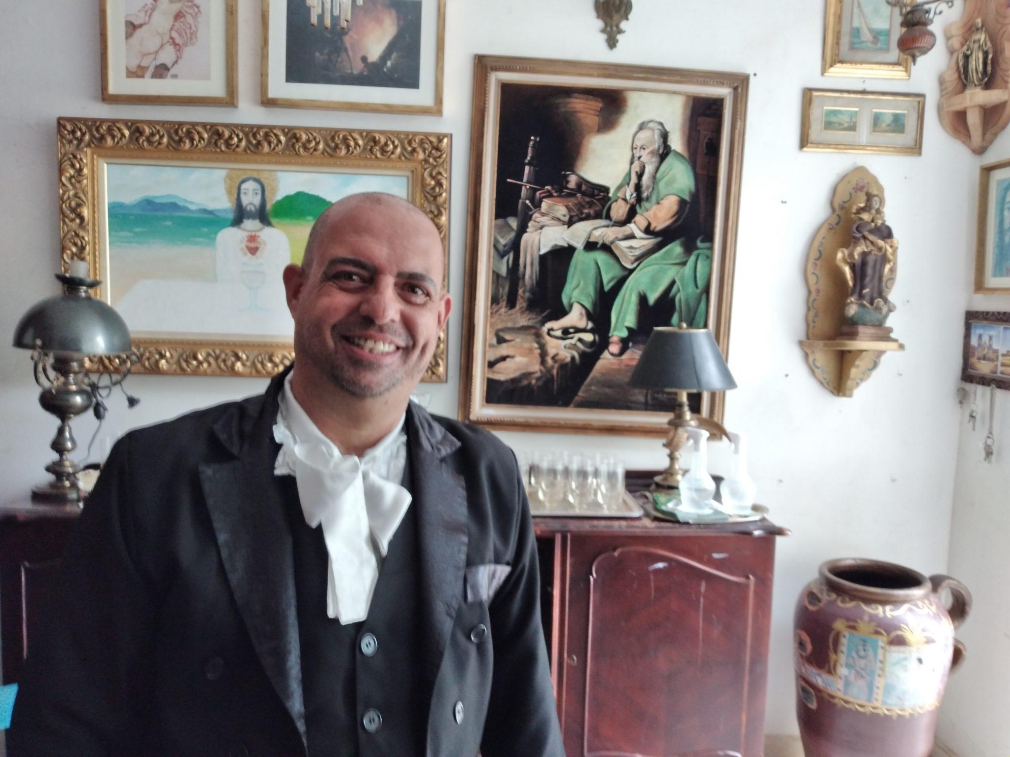 O ator Rômulo Vaz, no Antiquário e Brechó Goiano. Ao fundo, aparece quadros, móveis e outros itens do antiquário.